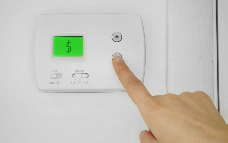A homeowner in Fresno, CA, setting up their programmable thermostat to save on energy costs.