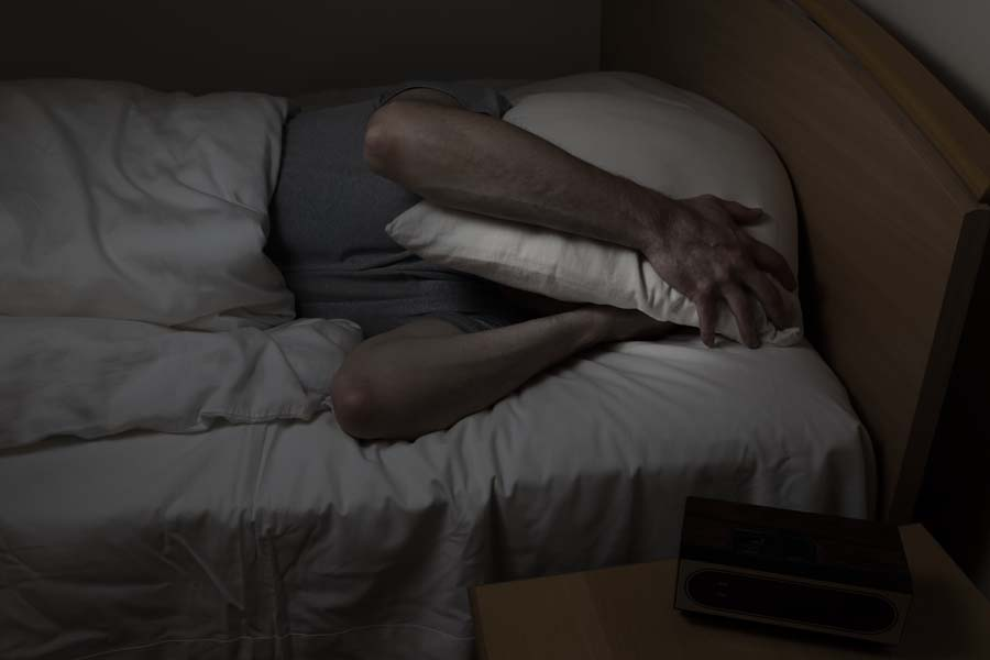 Man with a pillow over his head due to loud air conditioner.