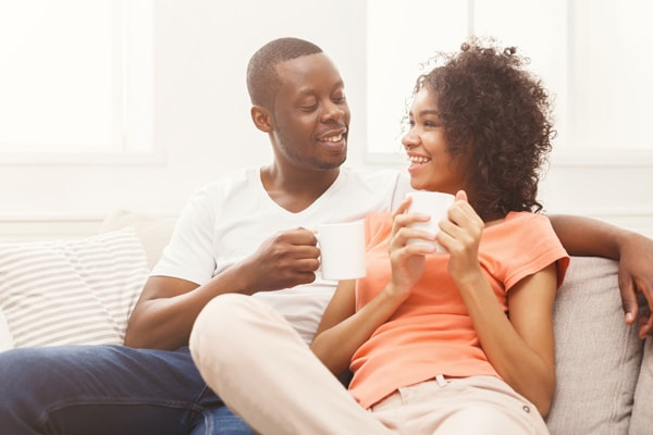 Smiling black couple drinking coffee at home.