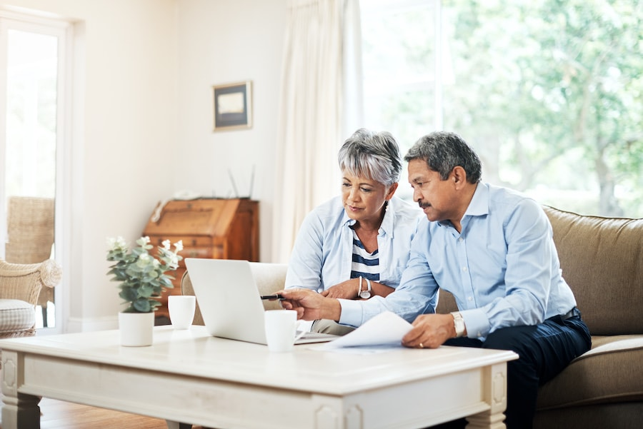 Mature couple researching heating and cooling options on a laptop computer at home.