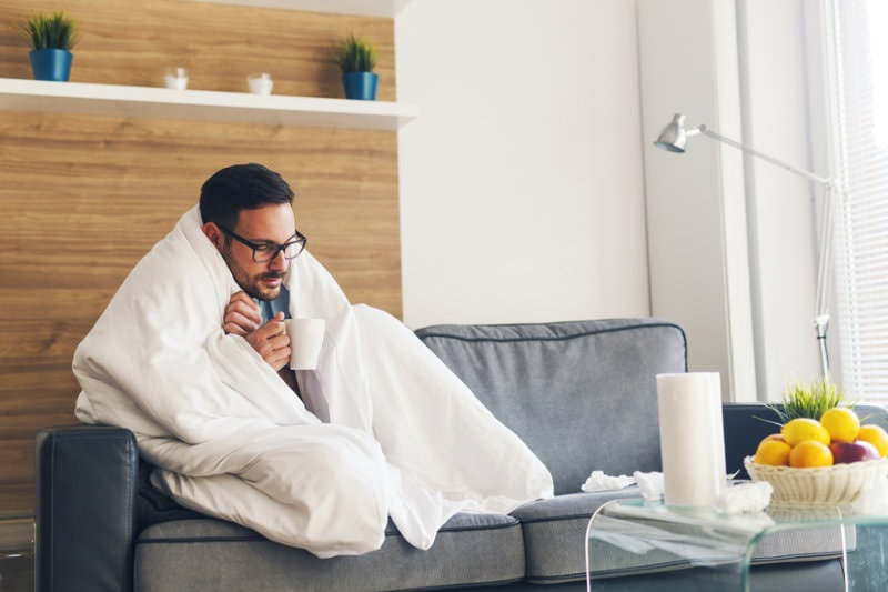 Man wrapped in a blanket sitting on a couch during an HVAC emergency.